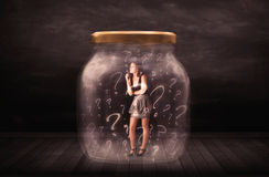 Businesswoman locked into a jar with question marks concept Stock Photography