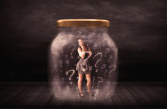 Businesswoman locked into a jar with question marks concept Stock Photo