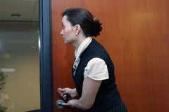 Businesswoman Locking the Door. Caucasian businesswoman looking through a glass screen while working the lock on an office door stock photography