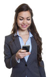 Businesswoman with long brown hair writing message with phone Stock Photo