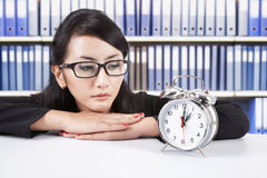 Businesswoman looking at alarm clock stock photo