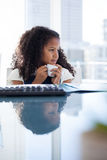 Businesswoman looking away while holding coffee cup at desk Stock Photography