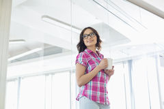 Businesswoman looking away while holding coffee mug in creative office Royalty Free Stock Photography
