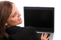 Businesswoman looking back over her should. Businesswoman working on laptop and looking back over her shoulder while smiling isolated on white Royalty Free Stock Photos