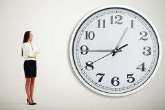 Businesswoman looking at big white clock Stock Photos