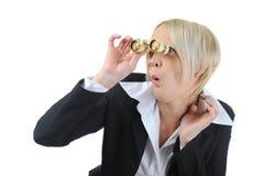 Businesswoman looking through binoculars Stock Photo
