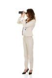 Businesswoman looking through binoculars. Royalty Free Stock Photography
