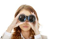 Businesswoman looking through binoculars. Stock Images