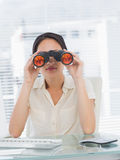 Businesswoman looking through binoculars at desk Stock Images