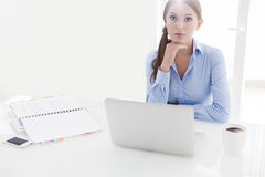 Businesswoman looking bored in front of laptop and television Royalty Free Stock Images