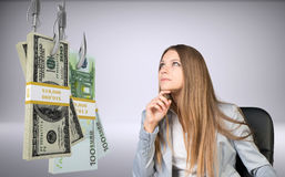 Businesswoman looking at bundle of money. Businesswoman in suprise sitting in chair and looking at bundles of money on fish-hooks on isolated grey background Stock Photography