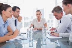 Businesswoman looking at camera with colleagues working around Royalty Free Stock Photo