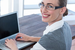 Businesswoman looking at camera with glasses and using laptop Royalty Free Stock Photo