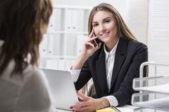 Businesswoman is looking at the camera. Her colleague is looking Stock Images