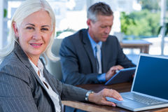 Businesswoman looking at camera while her colleague working Royalty Free Stock Photography