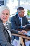 Businesswoman looking at camera while her colleague working Stock Image
