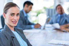 Businesswoman looking at camera while her colleague working Royalty Free Stock Images