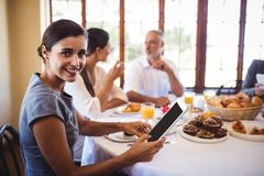 Businesswoman looking at camera while using digital tablet. In restaurant stock photo