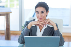 Businesswoman looking at camera and using her laptop Stock Photo