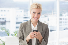 Businesswoman looking at camera and using her smartphone Stock Photo
