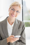 Businesswoman looking at camera and using her smartphone Stock Image