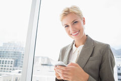 Businesswoman looking at camera and using her smartphone Stock Photos