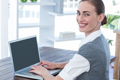 Businesswoman looking at camera and using laptop Stock Image