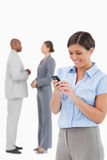 Businesswoman looking at cellphone with associates behind her Stock Images
