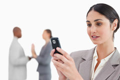 Businesswoman looking at cellphone with colleagues behind her Royalty Free Stock Photo