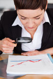 Businesswoman looking at a chart with a glass Stock Photography