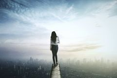 Businesswoman looking at the city from rooftop. Young businesswoman looking at the future city while standing on the rooftop Stock Image