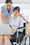 Businesswoman looking at co workers laptop who is sitting in whe Stock Image