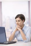 Businesswoman looking at computer screen. Sitting in office, concentrating Royalty Free Stock Photography
