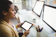 Businesswoman looking at computer while using digital tablet in creative office Stock Photo