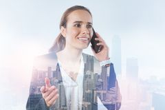 Businesswoman looking confused while talking on the phone. Urgent news. Strict elegant busy woman listening attentively to her interlocutor while holding a Royalty Free Stock Images