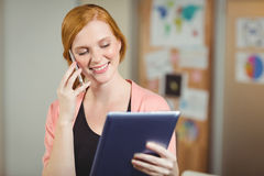 Businesswoman looking at digital tablet while talking on phone Royalty Free Stock Photo