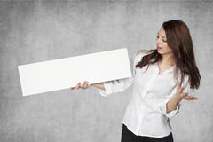 Businesswoman looking in disbelief at the advertisement Stock Photo