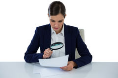Businesswoman looking at document through magnifying glass. Against white background stock photos