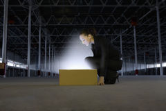 Businesswoman Looking At Glowing Box In Empty Warehouse. Full length side view of businesswoman looking at glowing box in empty warehouse Stock Photo