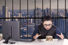 Businesswoman looking hamburger in office Stock Photos
