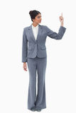 Businesswoman looking at hand while pointing up Stock Photos
