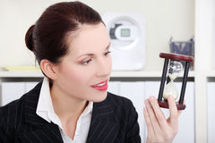 Businesswoman looking at hourglass. Pretty caucasian businesswoman looking at hourglass in the office Royalty Free Stock Photography