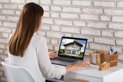 Businesswoman Looking At House On Laptop royalty free stock photos