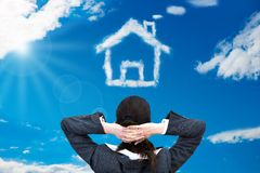 Businesswoman looking at house shaped cloud Royalty Free Stock Image