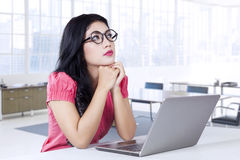 Businesswoman looking for idea in office Royalty Free Stock Image