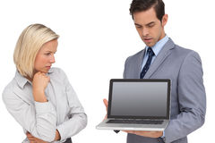 Businesswoman looking at laptop held by her colleague Stock Photography