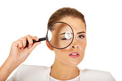 Businesswoman looking into a magnifier and have a big eye Stock Image
