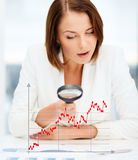Businesswoman looking through magnifier to graphs. Business, documents, statistics and people concept - businesswoman looking through magnifier to graphs in Stock Image