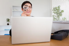 Businesswoman looking through  a magnifying glass Stock Images