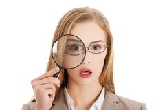 Businesswoman looking into a magnifying glass Stock Photo